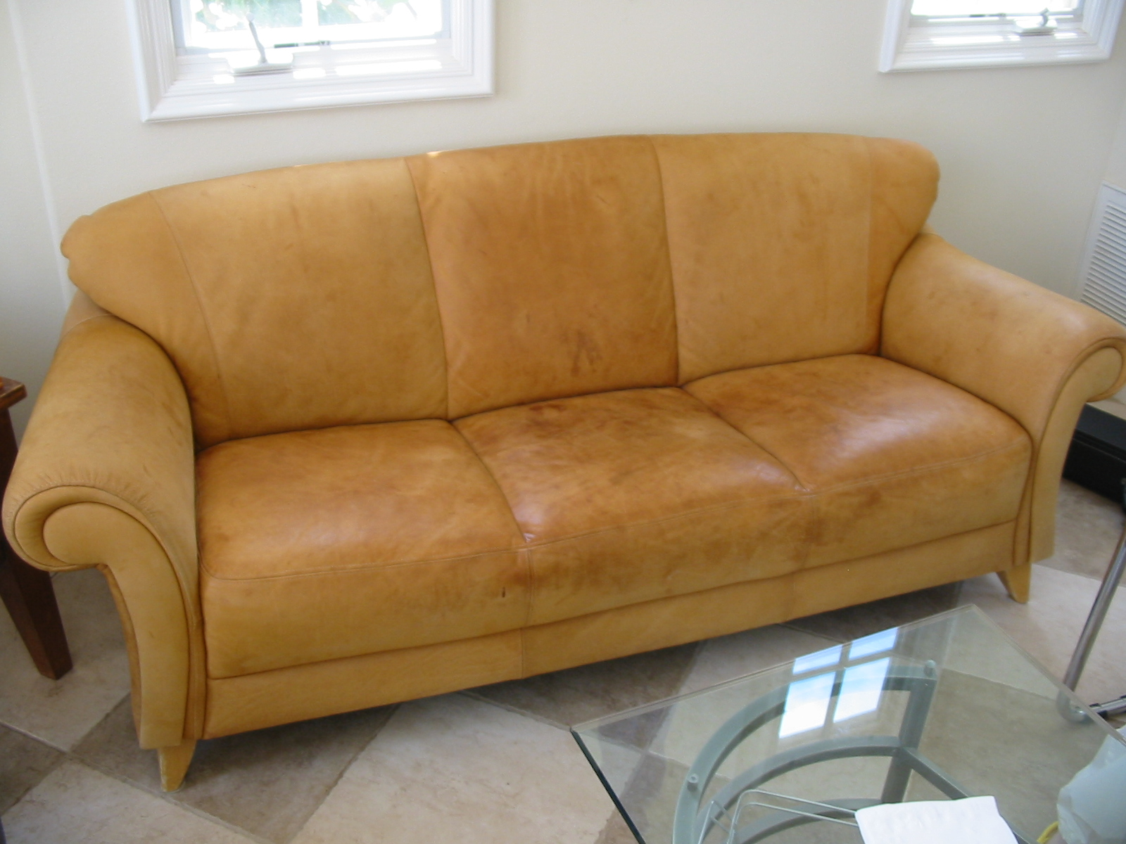 Faded and stained analine leather sofa.